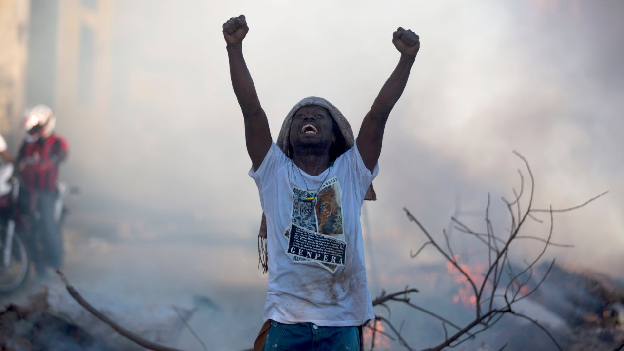 A demonstrator stands in the street chanting slogans against President Jovenel Moise during a protest to demand his resignation and to know how Petro Caribe funds have been used by the current and past administrations, in Port-au-Prince, Haiti. Much of the financial support to help Haiti rebuild after the 2010 earthquake comes from Venezuela's Petro Caribe fund, a 2005 pact that gives suppliers below-market financing for oil and is under the control of the central government. (Image: AP)