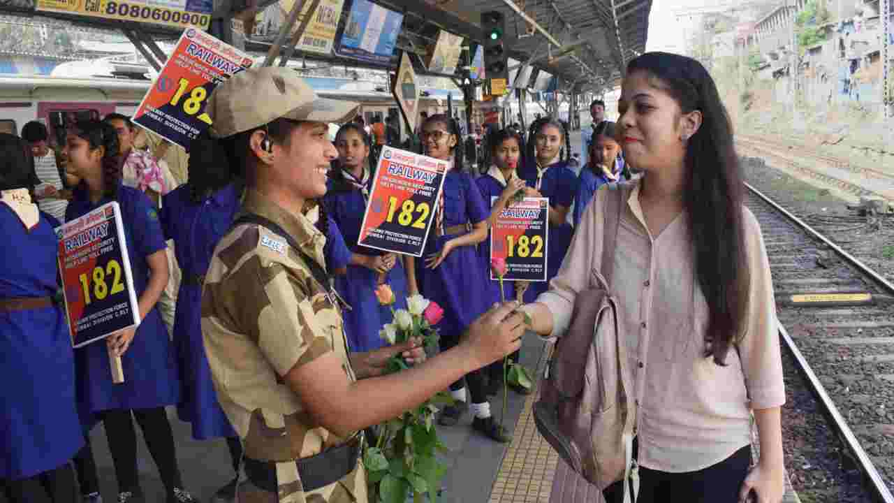 A Railway Protection Force woman personnel offers a rose to a woman commuter on the occasion of International Women's Day, in Mumbai. (Image: PTI)