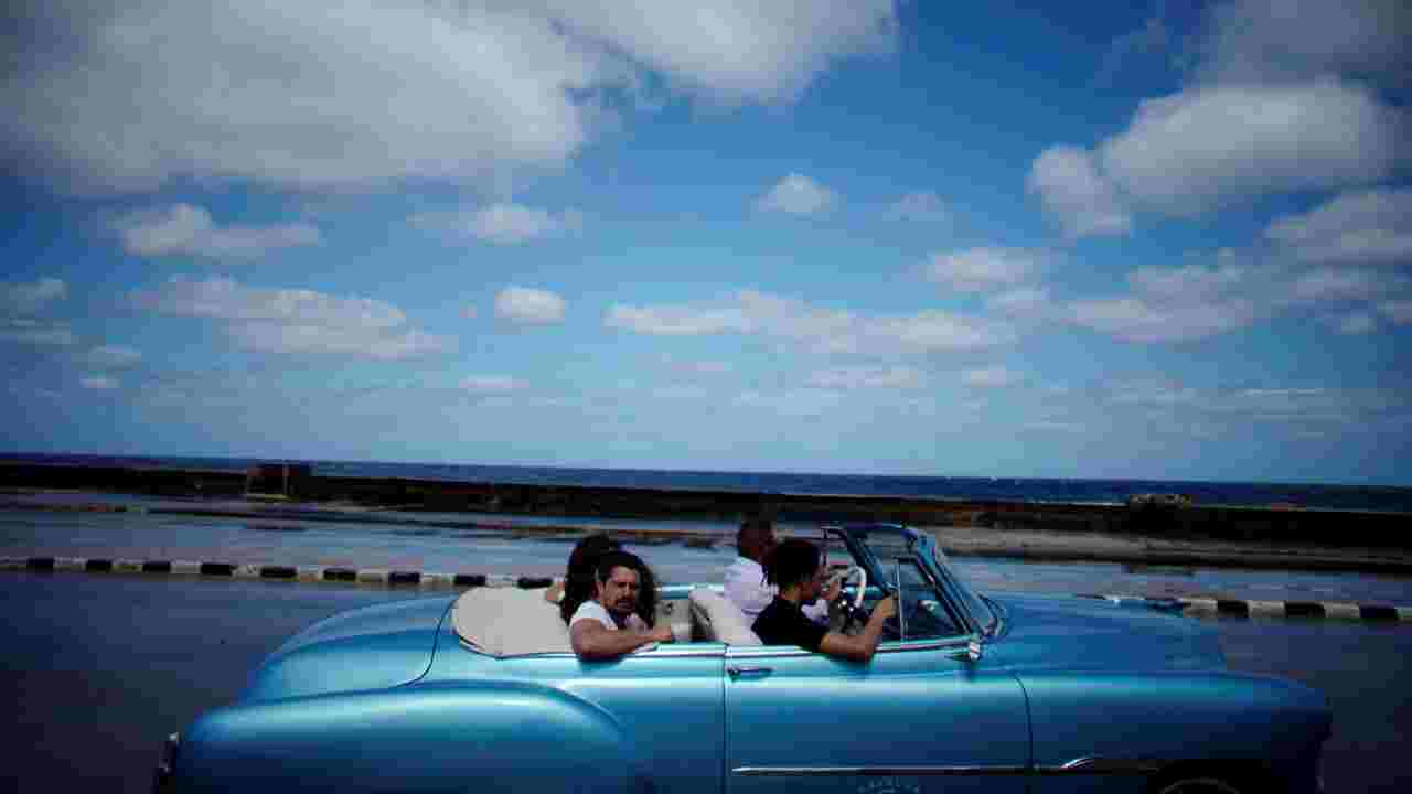 Tourists ride in a vintage car at the seafront Malecon in Havana, Cuba. (Image: Reuters)