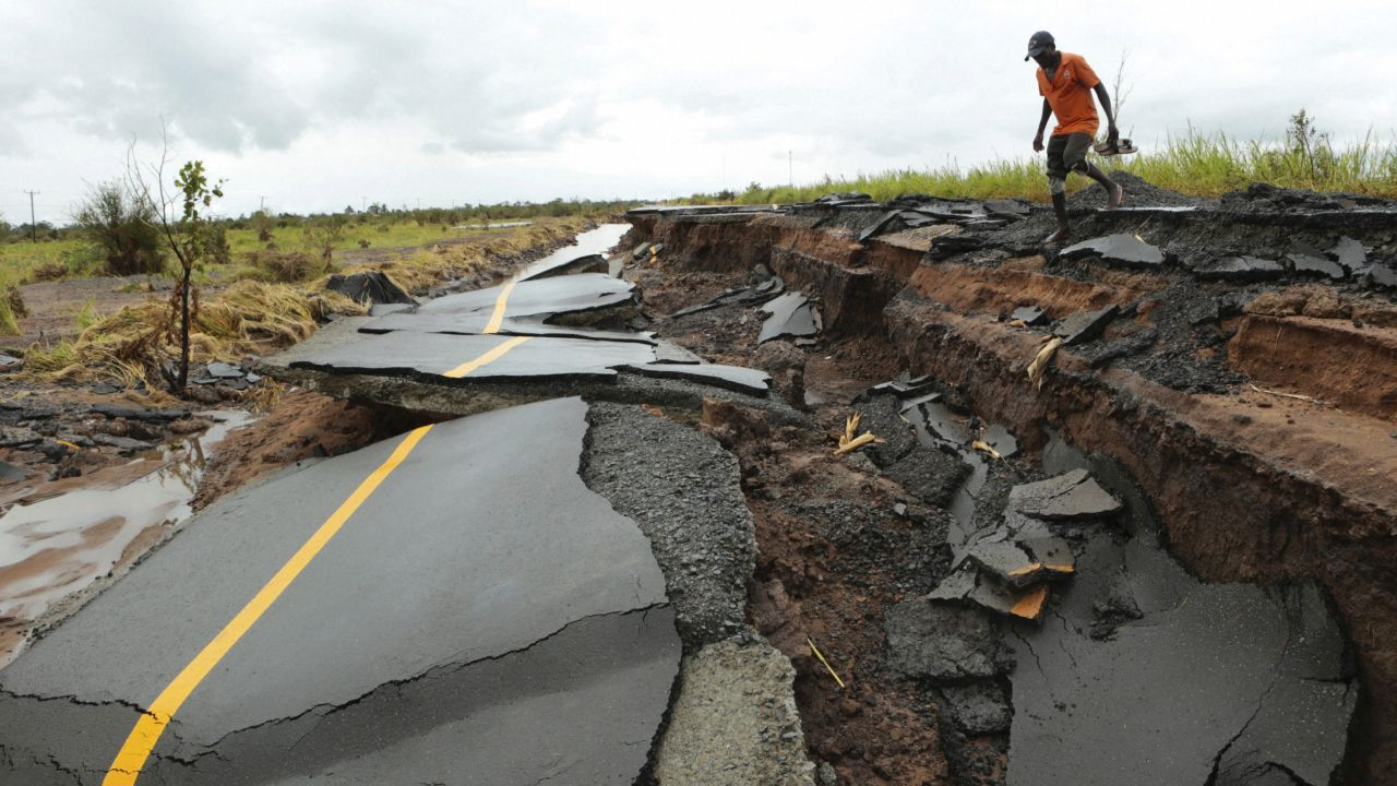 A man passes through a section of the road damaged by Cyclone Idai in Nhamatanda about 50 kilometres from Beira, in Mozambique. As flood waters began to recede in parts of Mozambique, fears rose that the death toll could soar as bodies are revealed. (AP/PTI)