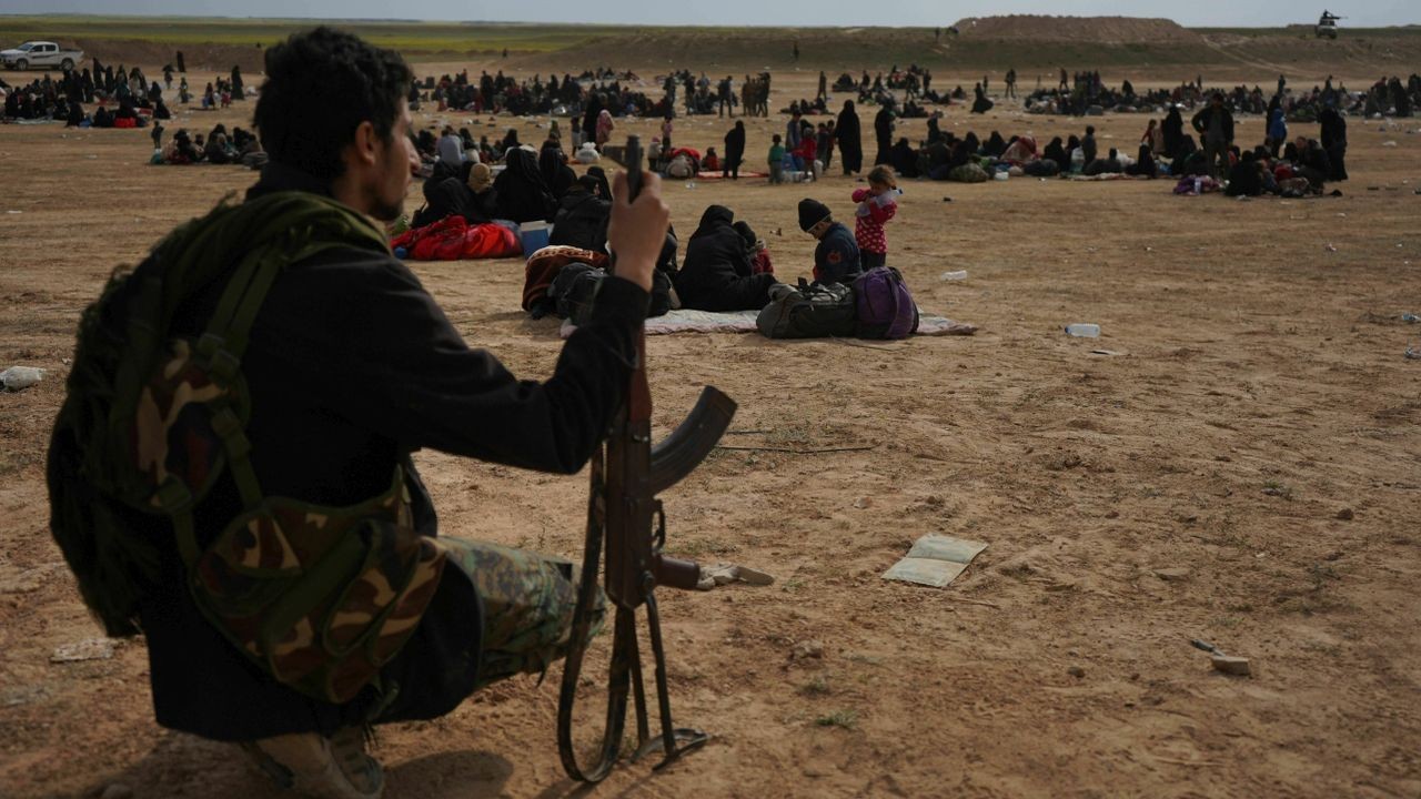 A member of US-backed Syrian Democratic Forces (SDF) watches over people who were evacuated out of the last territory held by Islamic State militants, outside Baghouz, Syria. Hundreds of people over the past two days streamed out of Baghouz, the last village held by the Islamic State group, under stepped-up assault the past four days by US-backed forces. (AP/PTI)
