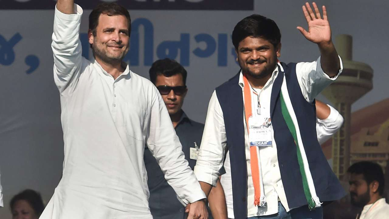 Rahul Gandhi shakes hands with Patidar leader Hardik Patel as he joins Congress, during a public meeting, in Gandhinagar. (Image: PTI)