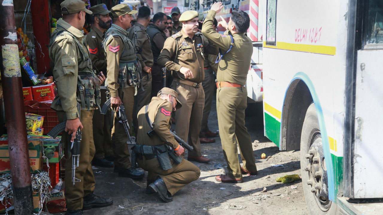 Police personnel inspect the site after a powerful explosion at a bus stand, in Jammu, Jammu and Kashmir. (Image: PTI)