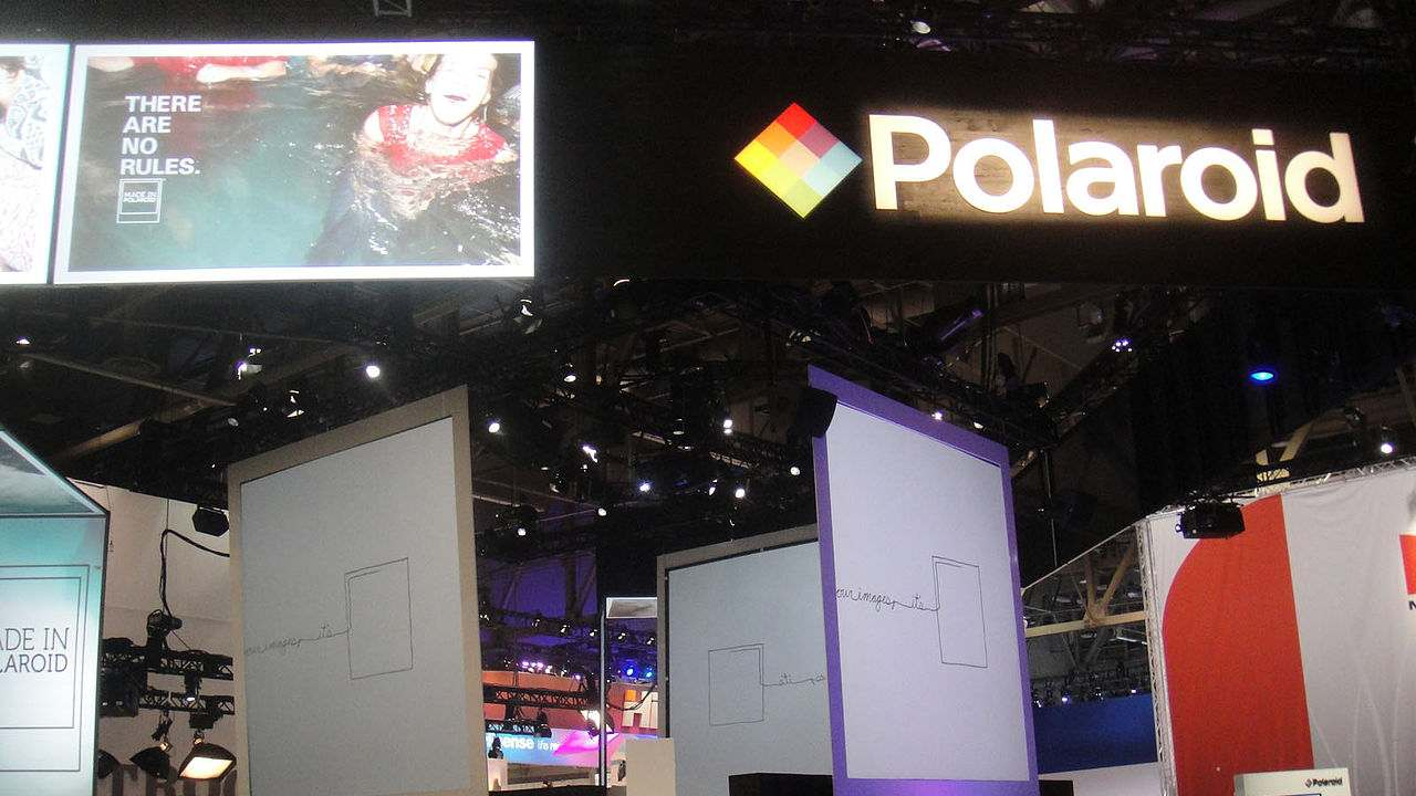 """Q8. Invented by Polaroid founder, employs diffusion transfer to move the dyes from the negative to the positive via a reagent. A negative sheet was exposed inside the camera, then lined up with a positive sheet and squeezed through a set of rollers which spread a reagent between the two layers, creating a developing film """"sandwich"""". The negative developed quickly, after which some of the unexposed silver halide grains were solubilized by the reagent and transferred by diffusion from the negative to the positive. After a minute, the back of the camera was opened and the negative peeled away to reveal the print. What was it called? (Image: Wikimedia Commons)"""