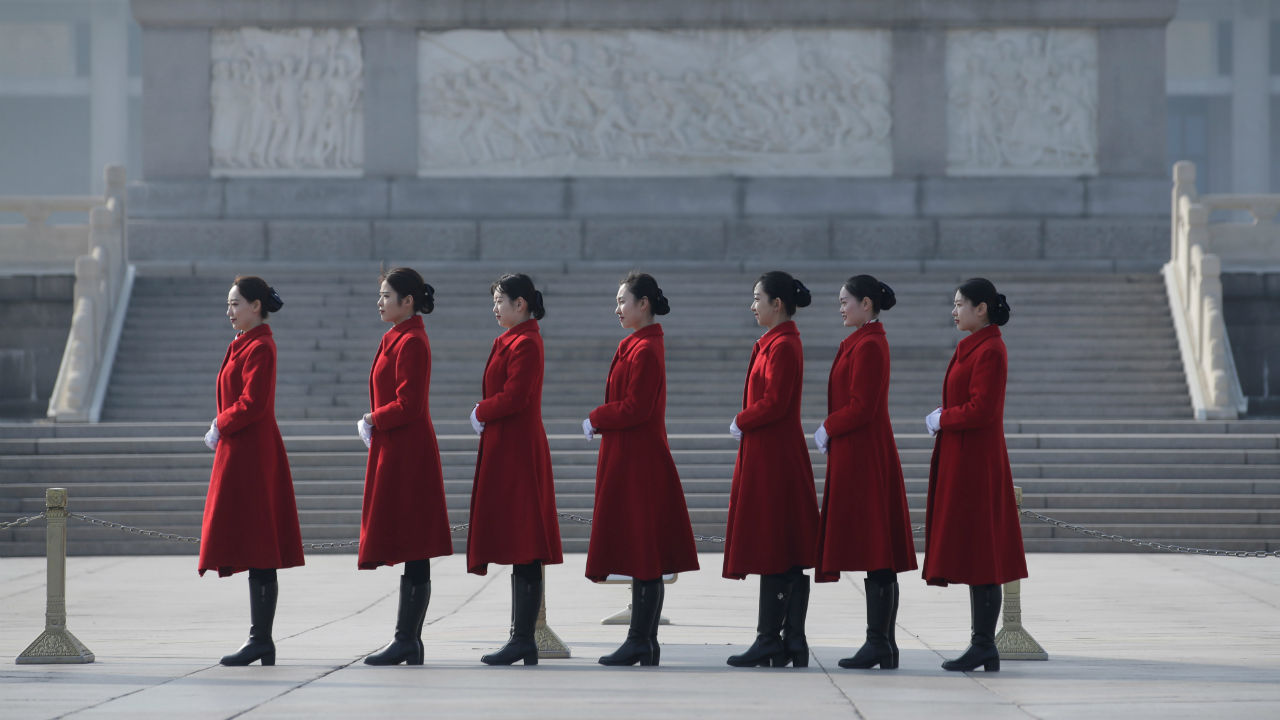 Attendants stand in a line for a photo at Tiananmen Square during a preliminary meeting ahead of National People's Congress (NPC), China's annual session of parliament, at the Great Hall of the People in Beijing, China. (Image: Reuters)