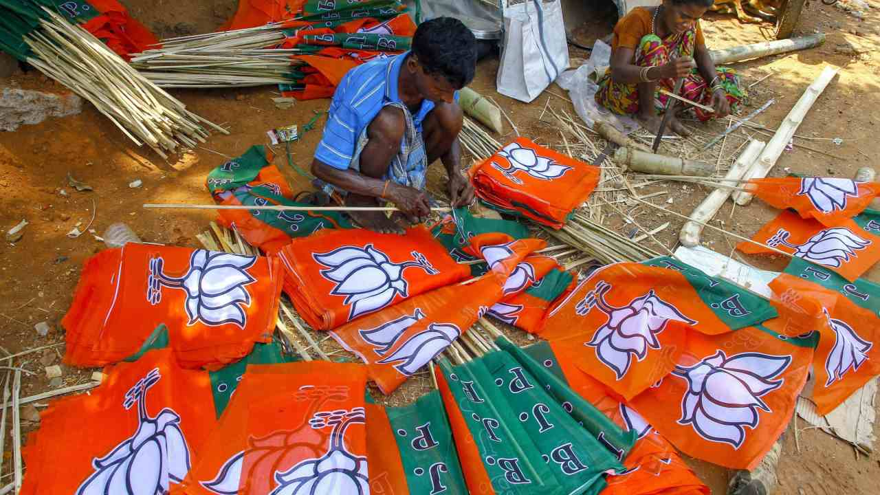 Workers prepare BJP party flags ahead of General Elections 2019, in Bhubaneswar, Tuesday, March 12, 2019. (Image: PTI)