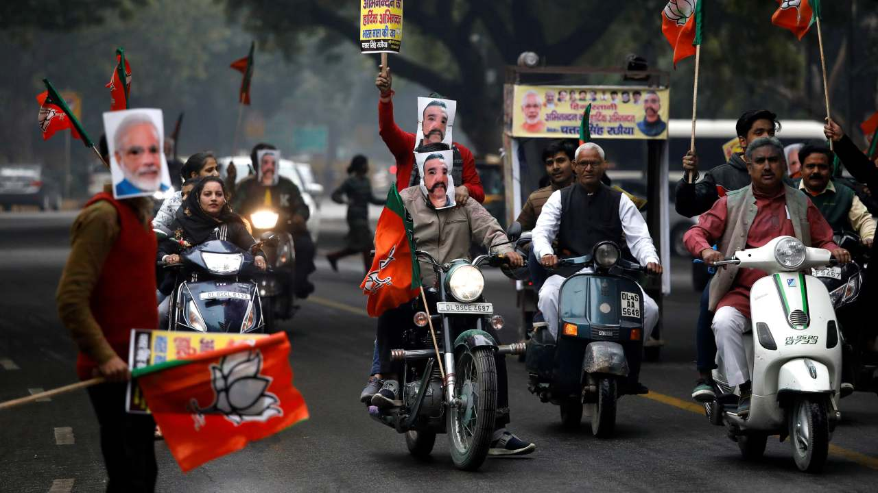 Supporters of India's ruling Bharatiya Janata Party (BJP) wearing masks of Indian Air Force pilot Wing Commander Abhinandan Varthaman and Prime Minister Narendra Modi ride their motorbikes during a rally to celebrate after Abhinandan was released by Pakistan, in New Delhi (REUTERS)