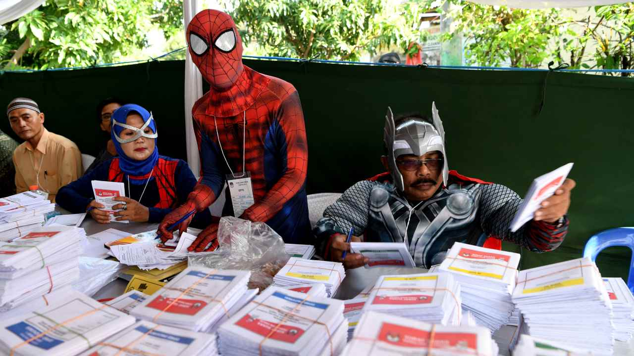 Election officials wearing superhero costumes prepare ballots at a polling station during elections in Surabaya, East Java province, Indonesia. (Image: Reuters)