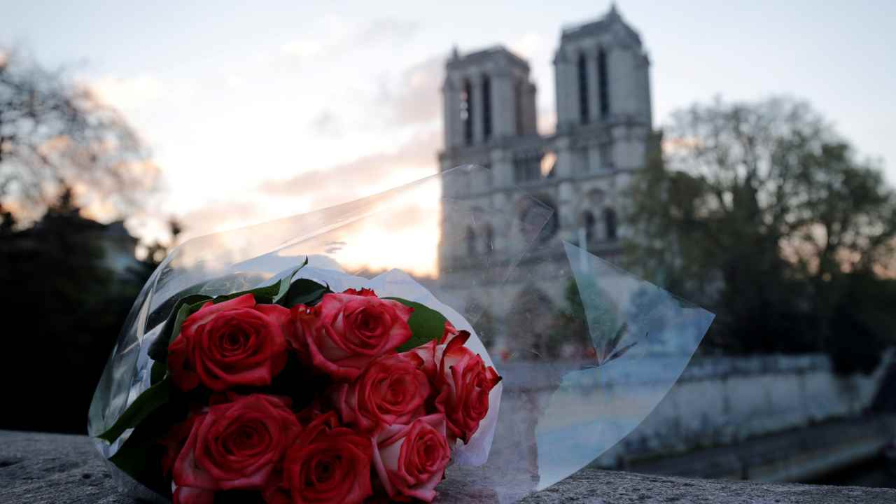 A bunch of roses placed near Notre-Dame Cathedral is pictured at sunrise after a massive fire devastated large parts of the gothic structure in Paris, France. (Image: Reuters)