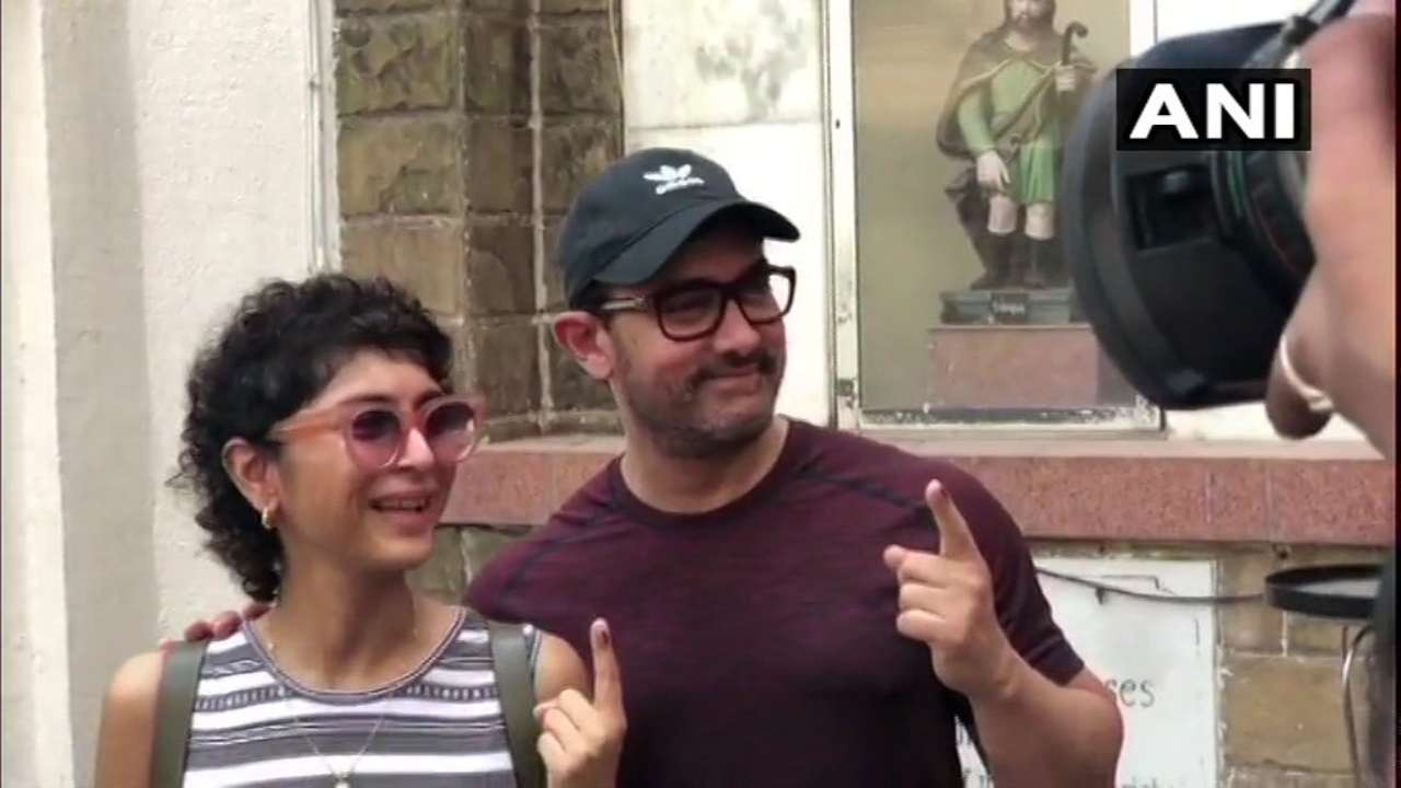 Actor Aamir Khan and his wife Kiran Rao posed with their inked fingers after casting their votes at polling booth in St Anne's High School in Bandra. (Image: ANI)