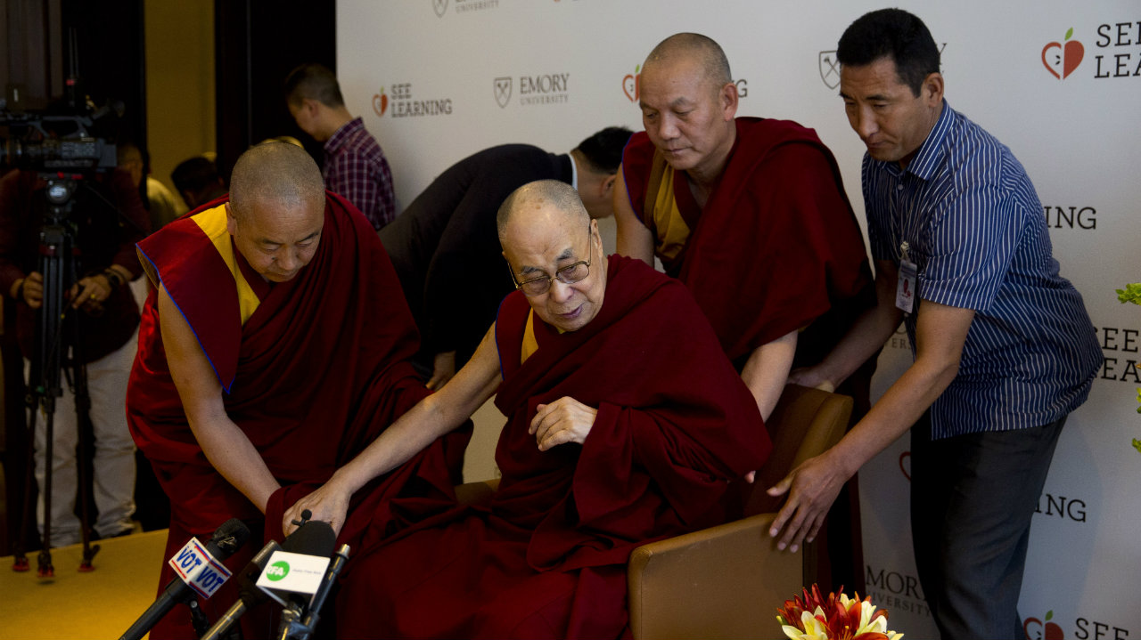 Tibetan spiritual leader the Dalai Lama (center) is assisted by his aides as he arrives to interact with an audience of educators, in New Delhi. (Image: AP)