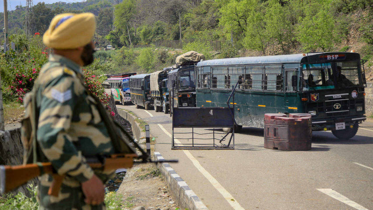 A BSF soldier stands guard near the national highway on the outskirts of Jammu. The government has banned civilian movement on strategic Srinagar-Jammu highway on two days in a week (Sunday and Wednesday) for smooth and safe passage of security forces convoys. (Image: PTI)