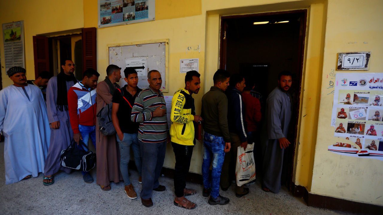 People wait to cast their votes during the second day of the referendum on draft constitutional amendments, at a polling station in Cairo, Egypt. (Image: Reuters)