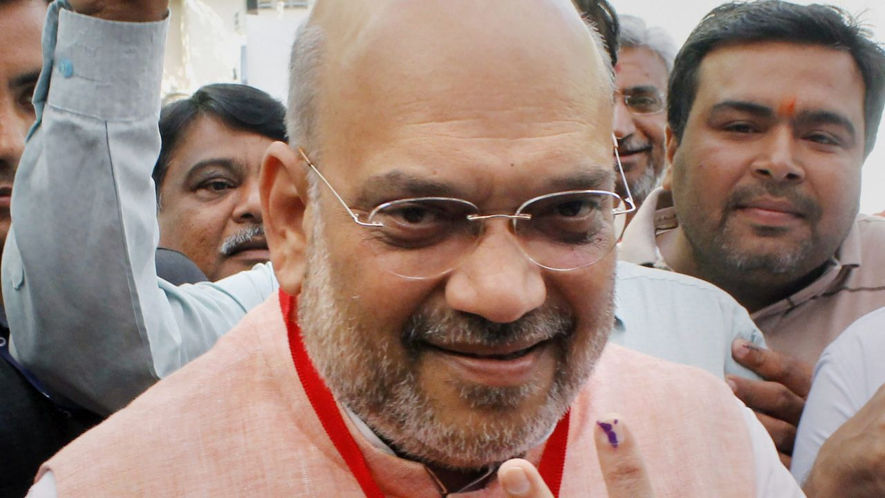 Bharatiya Janata Party (BJP) National President Amit Shah shows his inked finger after casting his vote during the third phase of the 2019 Lok Sabha elections, at a polling station in Ahmedabad, Gujarat. (Image: PTI)