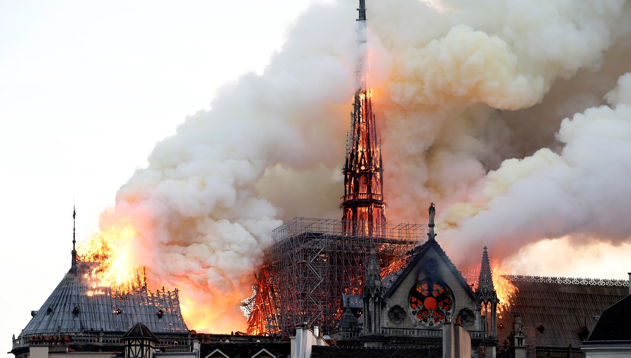 Smoke billows as fire engulfs the spire of Notre Dame Cathedral in Paris, France April 15, 2019. REUTERS/Benoit Tessier - RC14569C2380