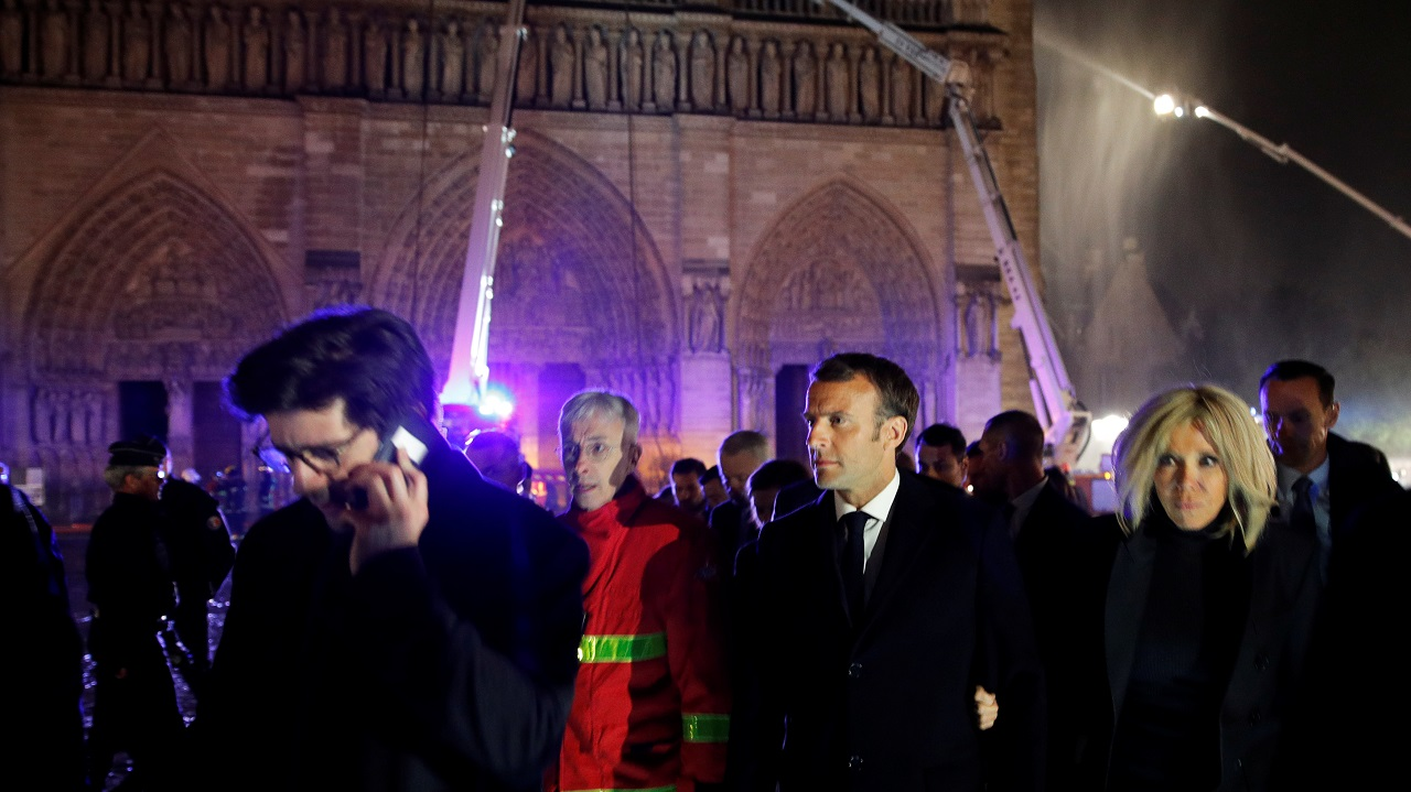 French President Emmanuel Macron and his wife Brigitte walk outside the Notre Dame Cathedral where a fire continues to burn in Paris, France, April 16, 2019. REUTERS/Philippe Wojazer/Pool - RC1B7B591700