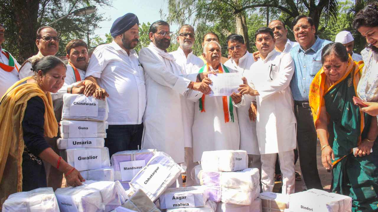 Senior Congress leader Suresh Pachouri and other party leaders hold lists of debt-ridden farmers after the party's loan waiver sceme, outside the residence of former Madhya Pradesh chief minister Shivraj Singh Chouhan, in Bhopal. (Image: PTI)
