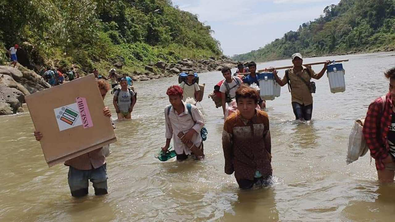 A polling team crosses river Kabung en-route to 34-Messing polling station under Siang district in Arunachal Pradesh. (Image: Twitter/@SpokespersonECI)