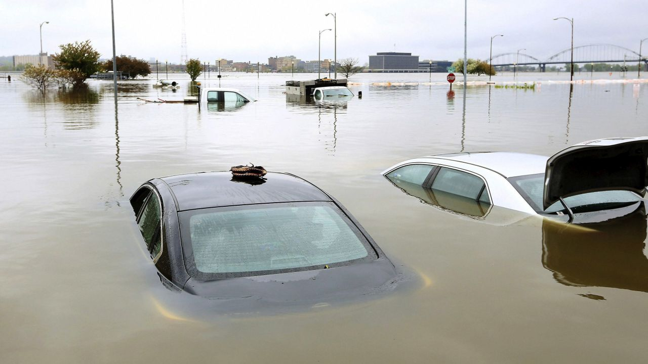 A baseball glove sits on the roof of one vehicle and the trunk of another is open as they sit in Mississippi River flood waters behind the Peterson Paper Co. Apartments in downtown Davenport, Iowa. (Image: AP/PTI)