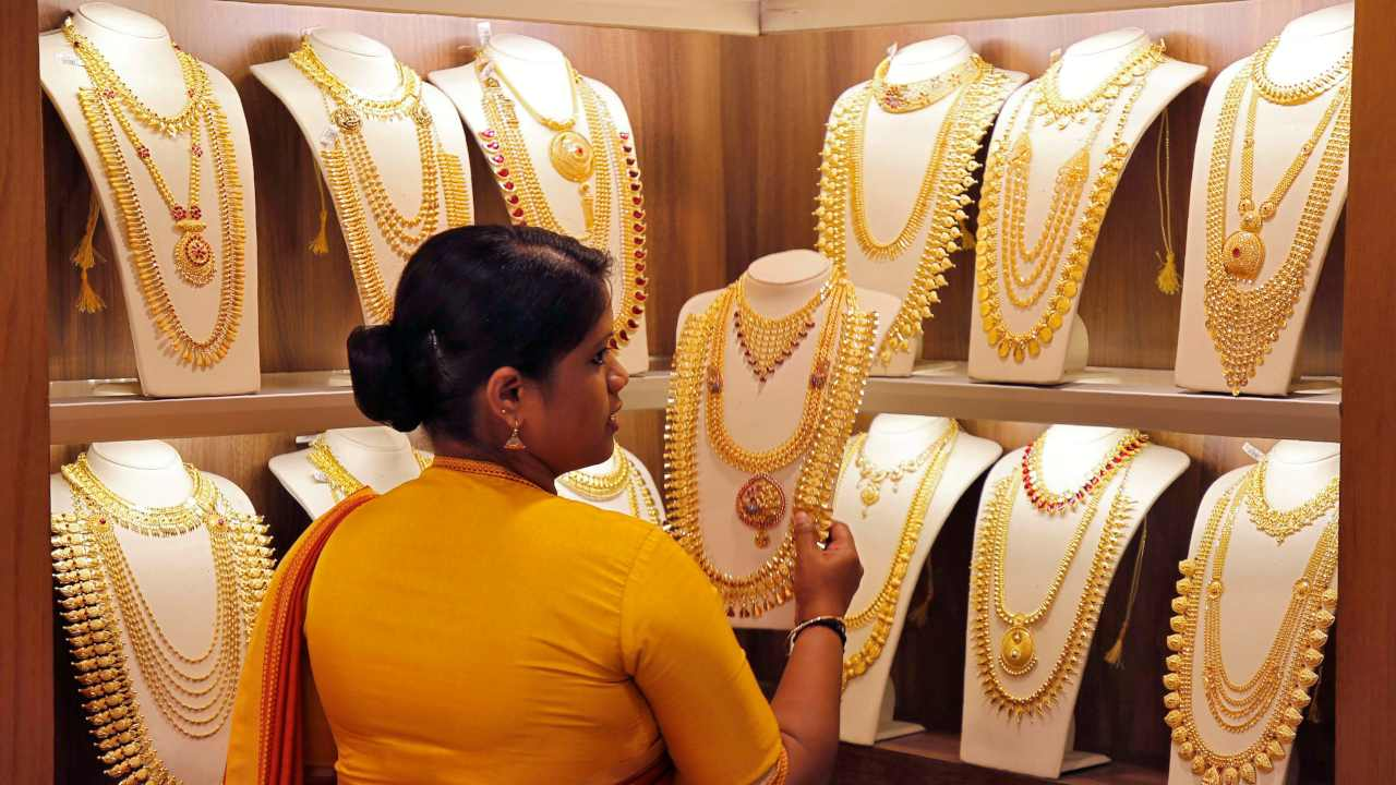 A saleswoman picks gold necklaces to show it to a customer inside a jewellery showroom on the occasion of Akshaya Tritiya, a major gold buying festival, in Kochi, India. (Image: Reuters)