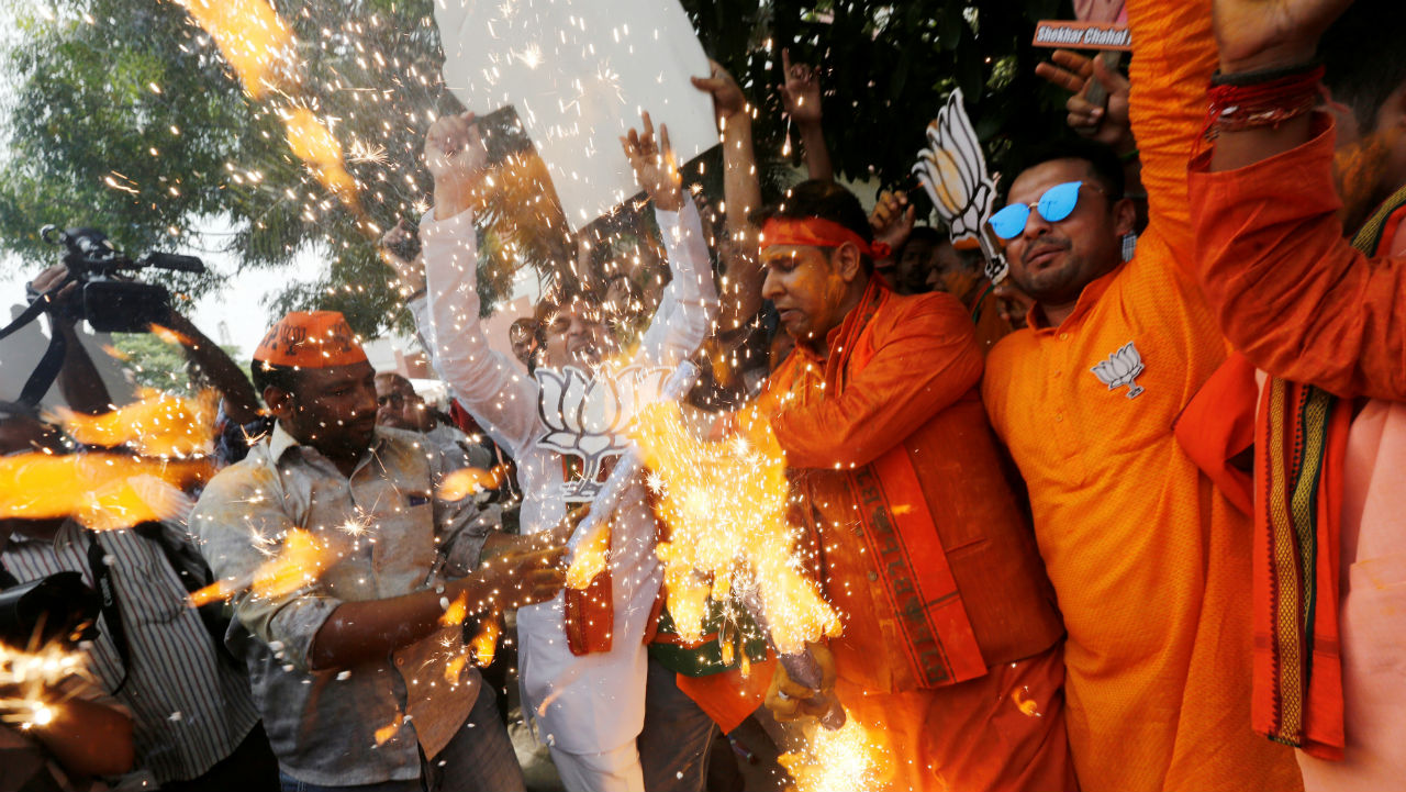 BJP supporters celebrate after learning the initial election results outside the party headquarters in New Delhi, India. (Image: Reuters)