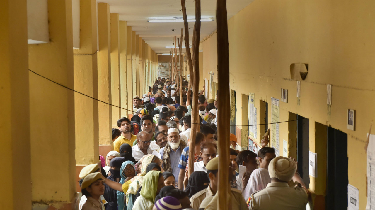 Voters queue to cast their votes at a polling station in Khajuri area of East Delhi. (Image: PTI)