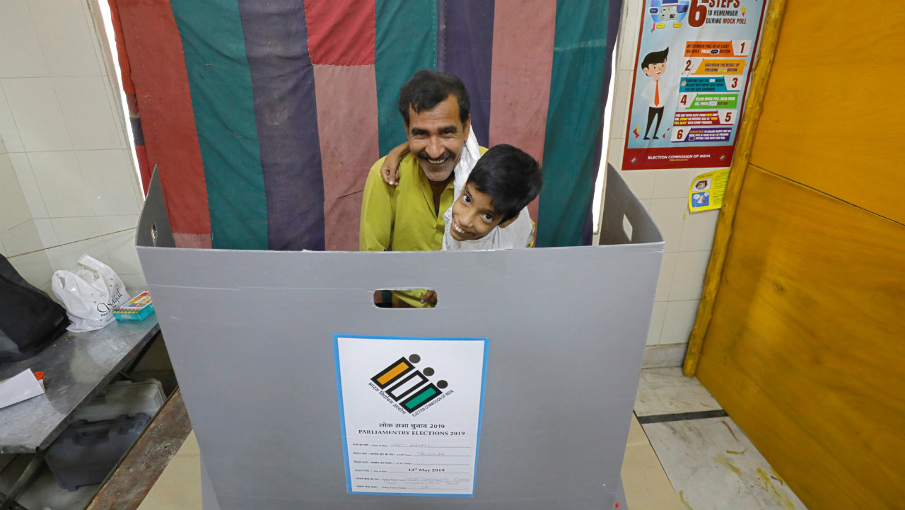 A man holding a child reacts behind a voting compartment as he prepares to cast his vote at a polling station in New Delhi. (Image: Reuters)