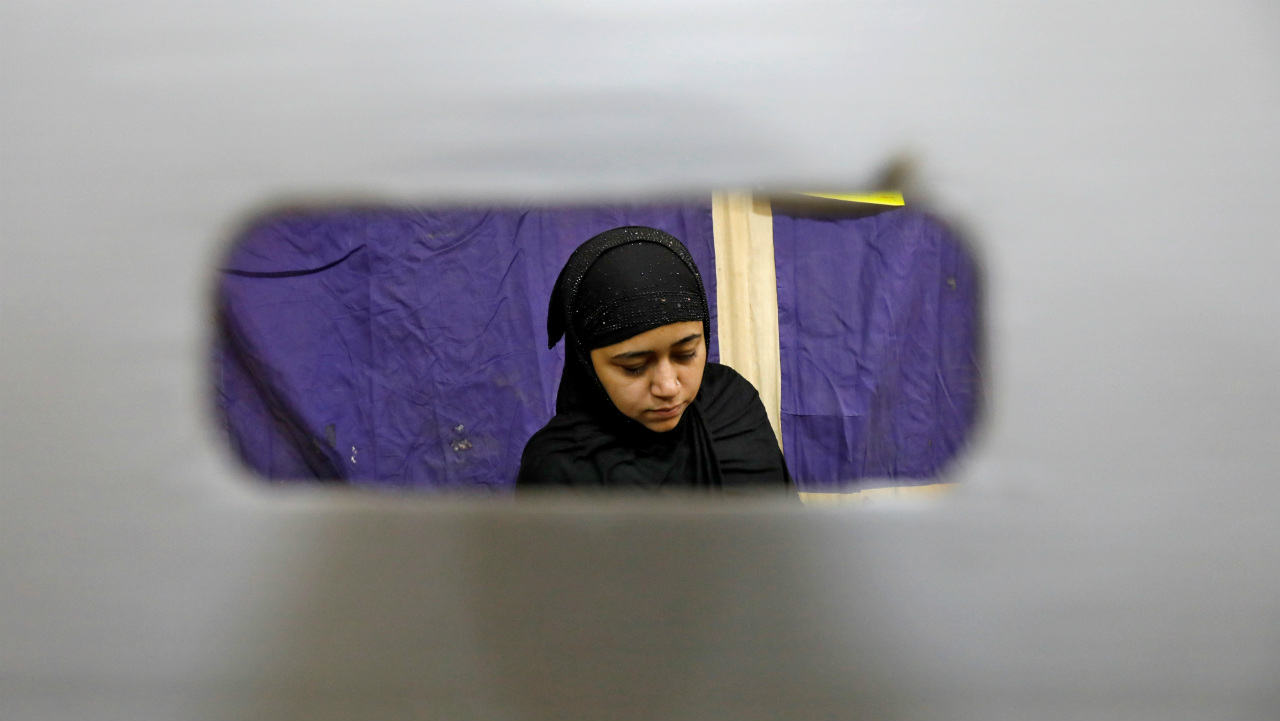 A woman is pictured through a voting compartment as she casts her vote at a polling station in New Delhi. (Image: Reuters)