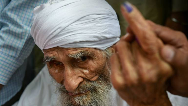 Bachan Singh ,111, the oldest voter in Delhi, leaves the polling booth after casting his vote in West Delhi. (Image: PTI)