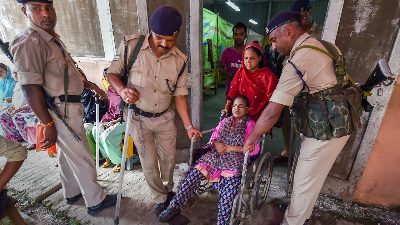 A differently-abled voter being helped by security personnel at a polling booth in Howrah district, West Bengal. (Image: PTI)