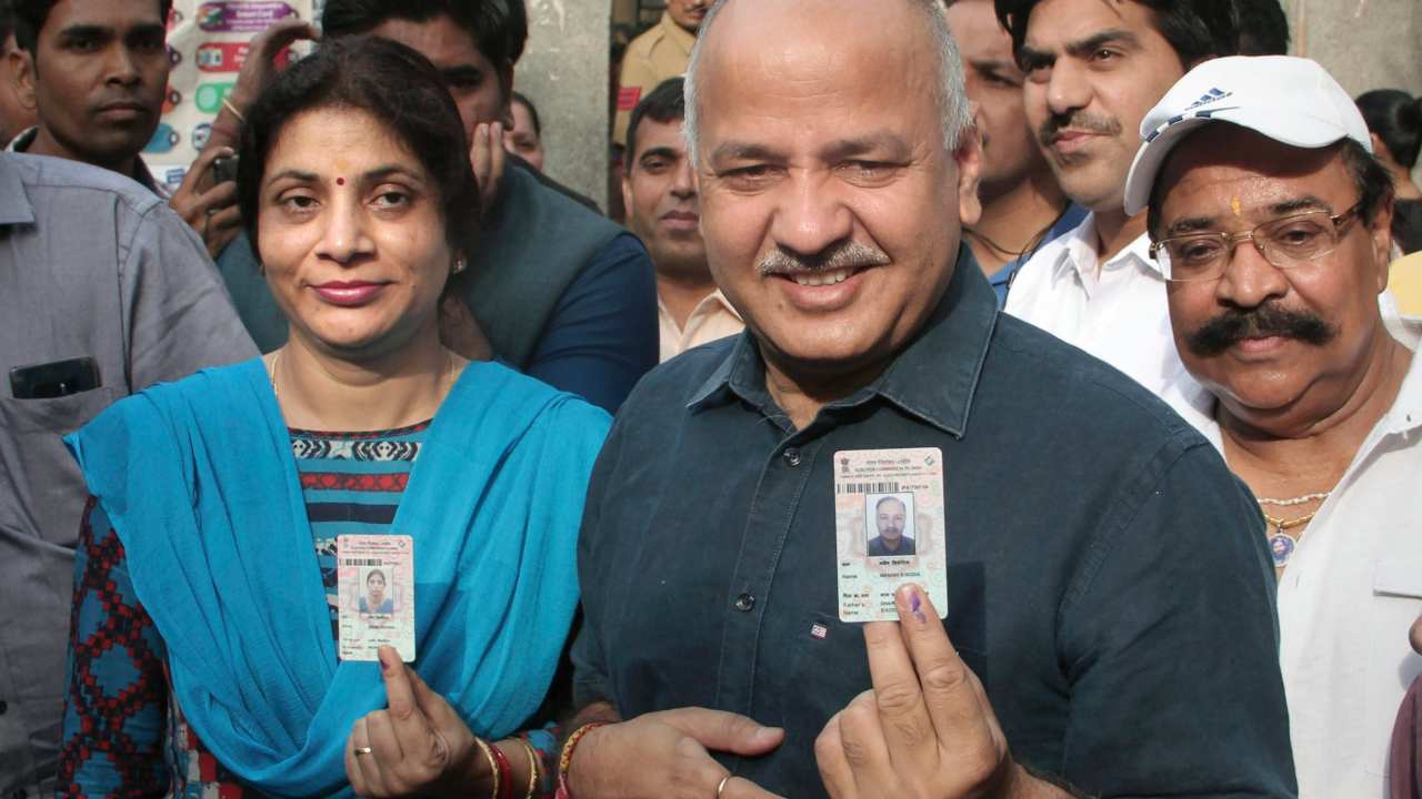 Delhi Deputy Chief Minister Manish Sisodia and his wife Seema Sisodia show their ID cards and finger marked with indelible ink after casting vote in East Delhi. (Image: PTI)