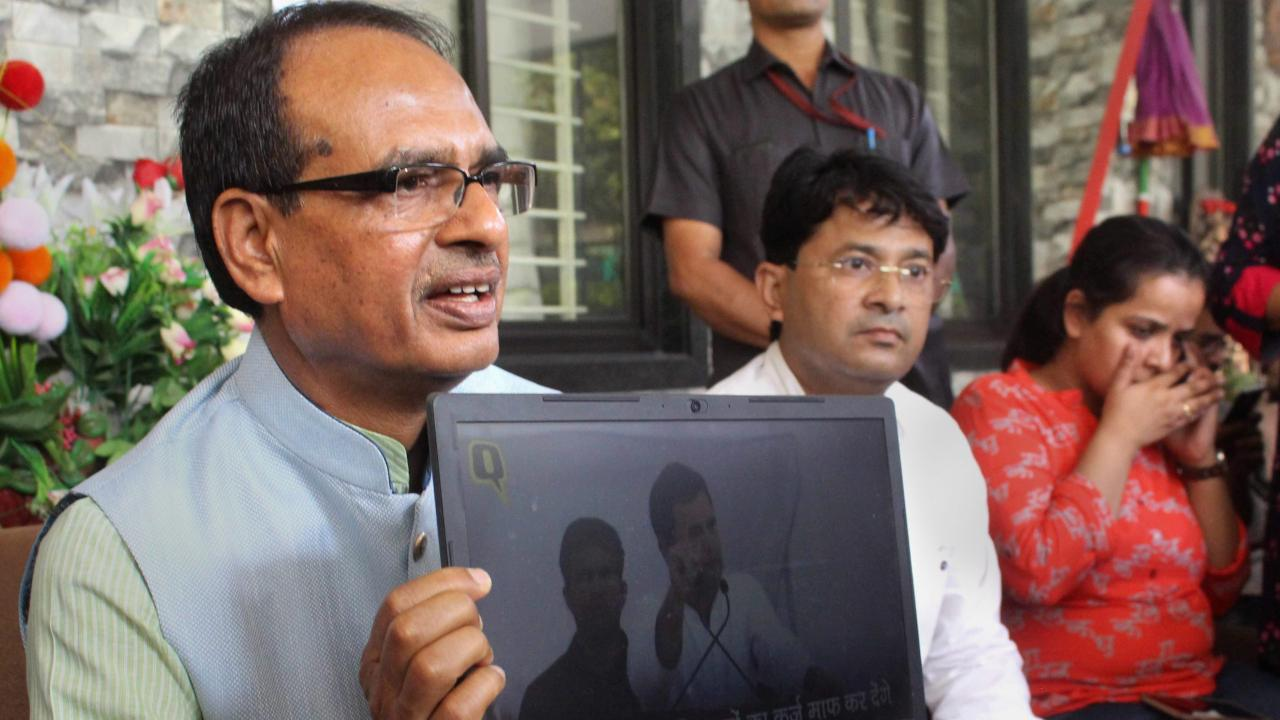 Former Madhya Pradesh chief minister Shivraj Singh Chouhan displays a video clip of Congress President Rahul Gandhi while addressing a press conference at his residence, in Bhopal. (Image: PTI)
