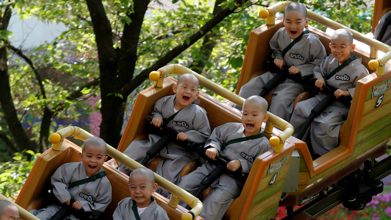 Boys who are experiencing the lives of Buddhist monks by staying in a temple for two weeks as novice monks, enjoy a ride at Everland amusement park in Yongin, South Korea. (Image: Reuters)