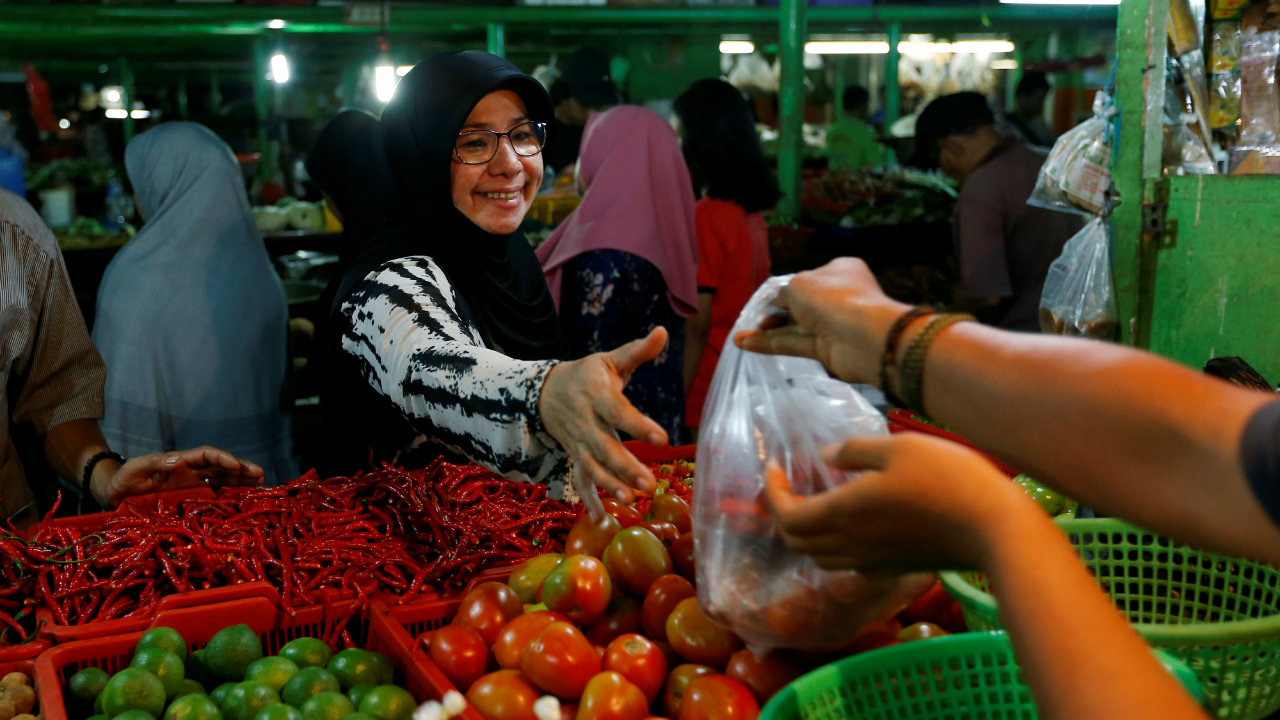 A woman takes a pack of goods from a seller as she shops at a traditional market in Jakarta, Indonesia. (Image: Reuters)