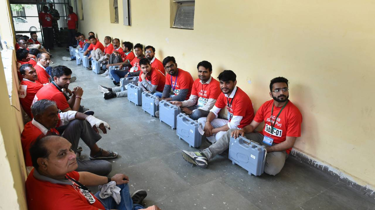 Election officials wait with EVMs ahead of counting at Nand Nagri counting center of East Delhi. (PTI)