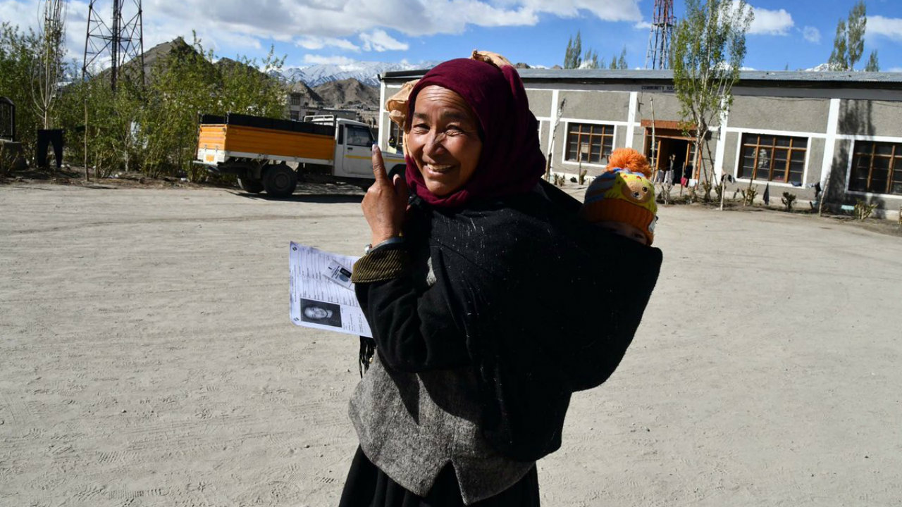 A voter carrying her child shows her inked finger in Ladakh. (Image: PIB India/Twitter)