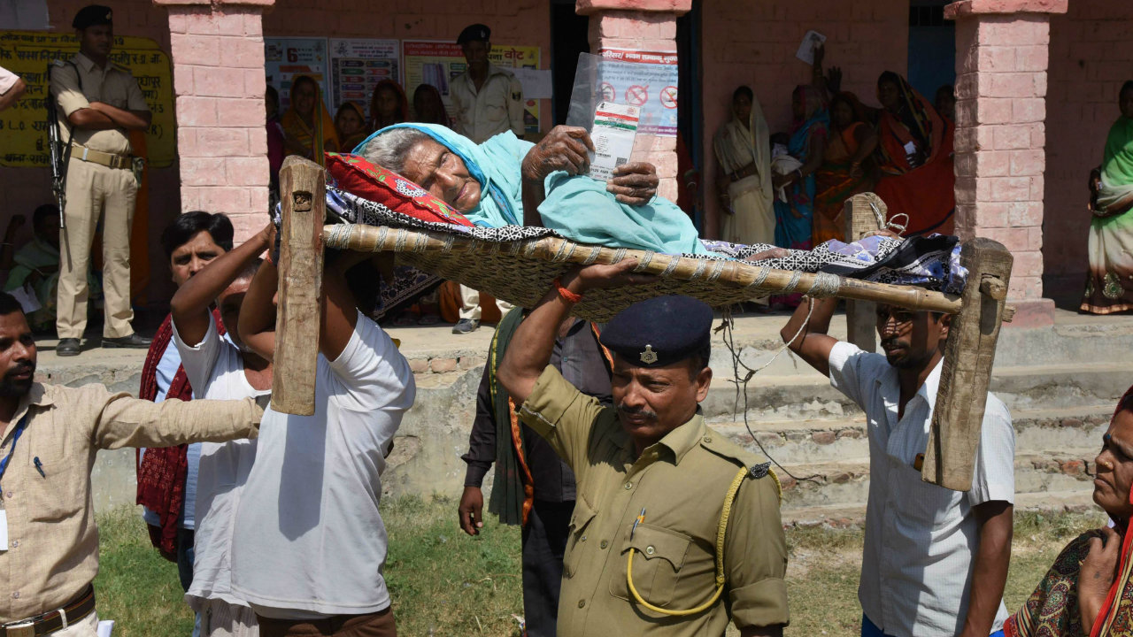 Security personnel carry an elderly woman to a polling station to cast vote during the fifth phase of the 2019 Lok Sabha elections, at Hajipur in Vaishali district, Bihar. (Image: PTI)