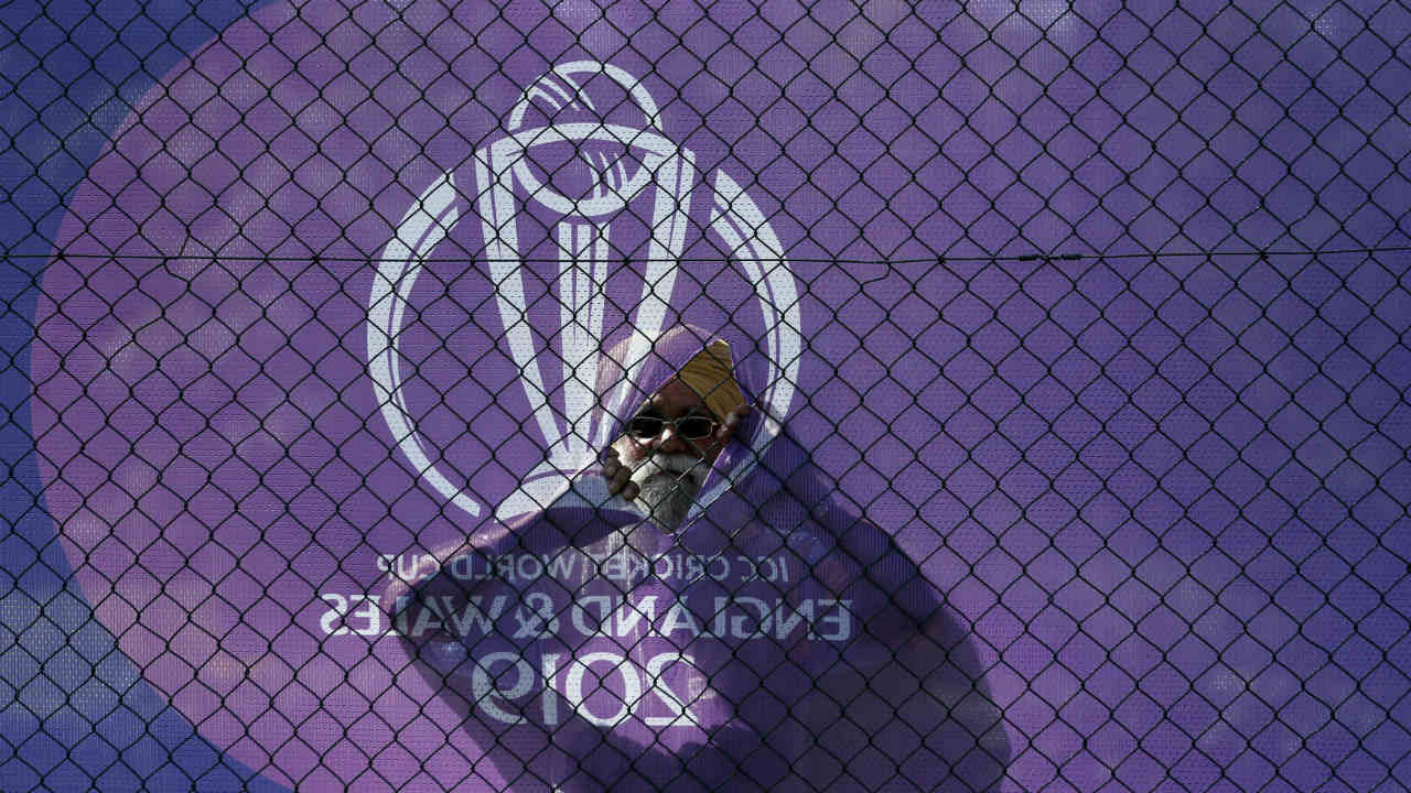 Anything to watch the 'Men in Blue'! A fan watches on through a gap in the fence as the Indian team practice. (Image: AP)