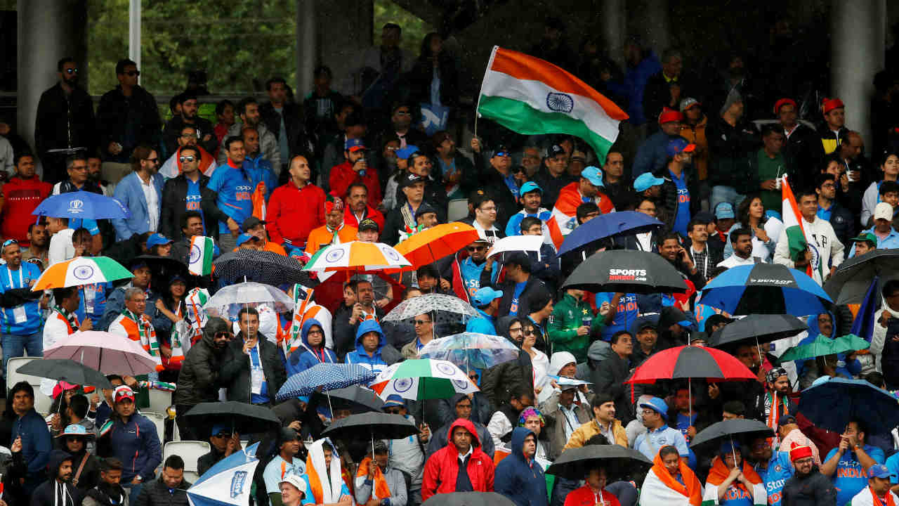 The spectators present in the stadium were forced to open their umbrellas as rains finally had its say in the match. India were 305/4 after 46.4 overs with Kohli and Vijay Shankar in the middle when the two umpires took the players off the field. (Image: Reuters)
