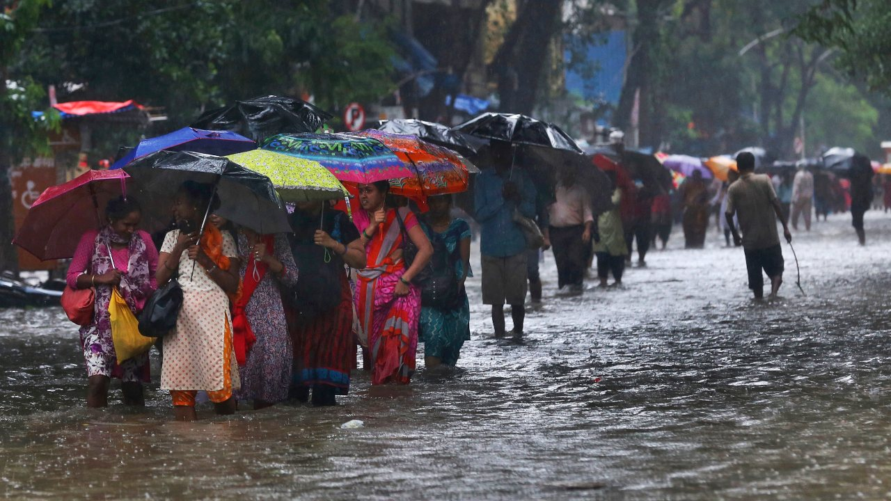 With the onset of monsoon, the city has been experiencing heavy rains over the past few days. Although waterlogging and traffic jams at several places in Mumbai have added to people's woes, nothing seems to be able to bring life to a pause in this city. Not even the rains! (Image: AP)