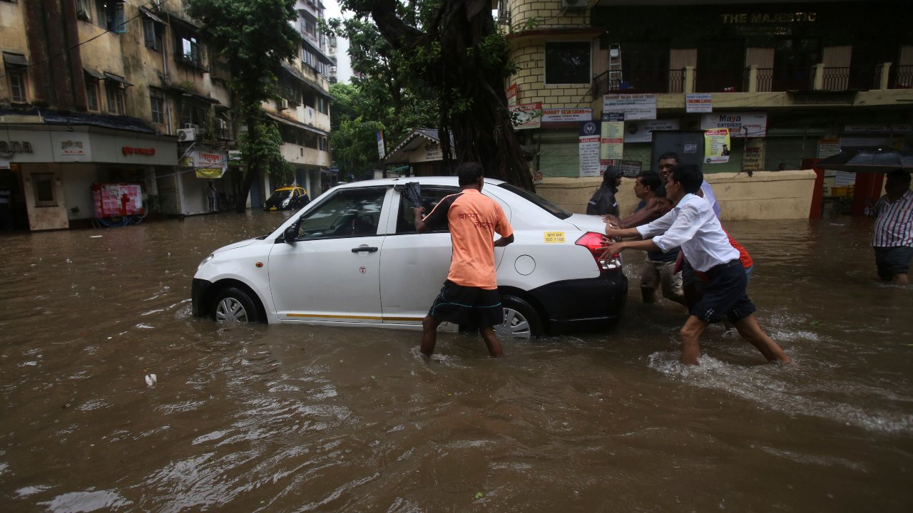 People push a car to a safer place from a waterlogged street. (Image: AP)