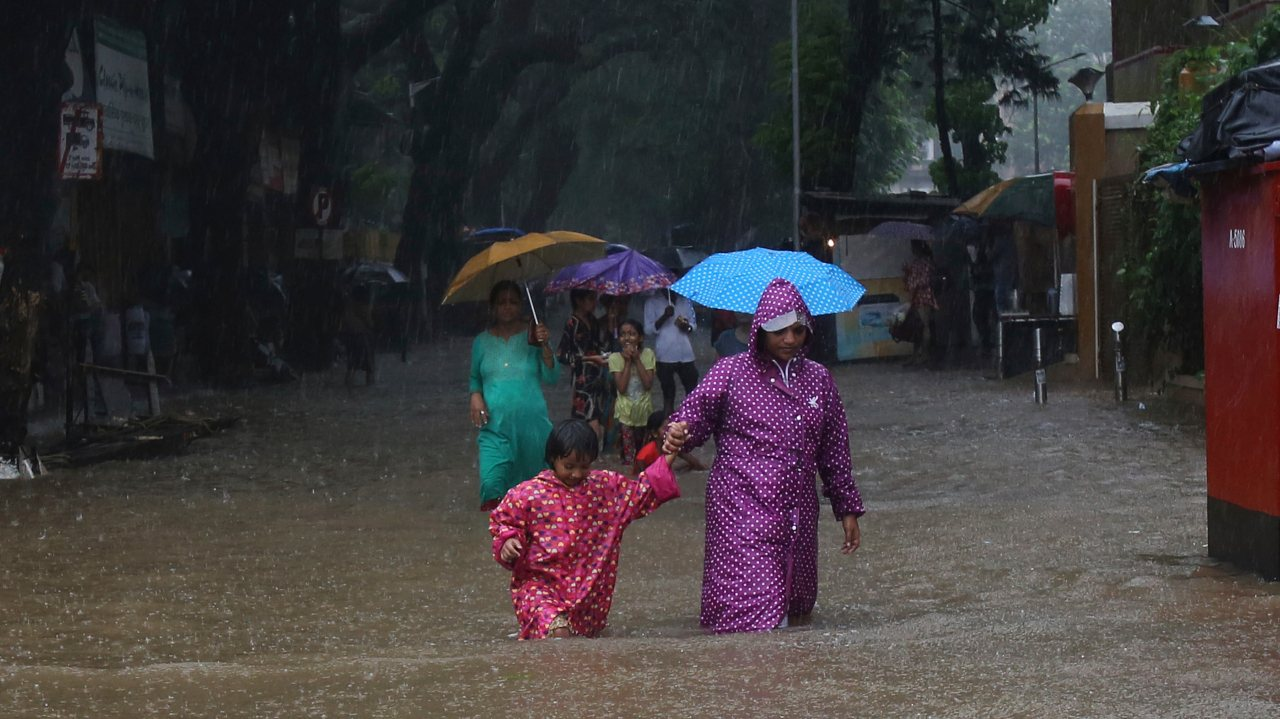 Mother and child wade through a waterlogged street in the city. (Image: AP)