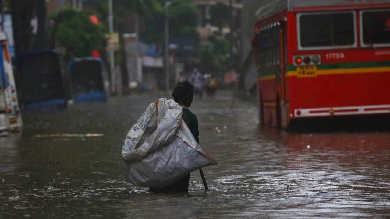 A ragpicker looks for waste items through a waterlogged street. (Image: AP)