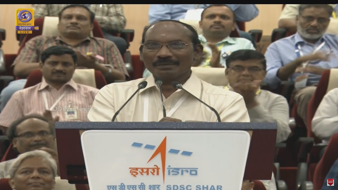 """ISRO Chairman K Sivan gives a press briefing after the successful launch of Chandrayaan 2. He said, """" It is a three-satellite mission stacked in a single launch mission. It is my duty to salute all the people who made this possible. Our task is not over."""" (Image: Screengrab DD)"""