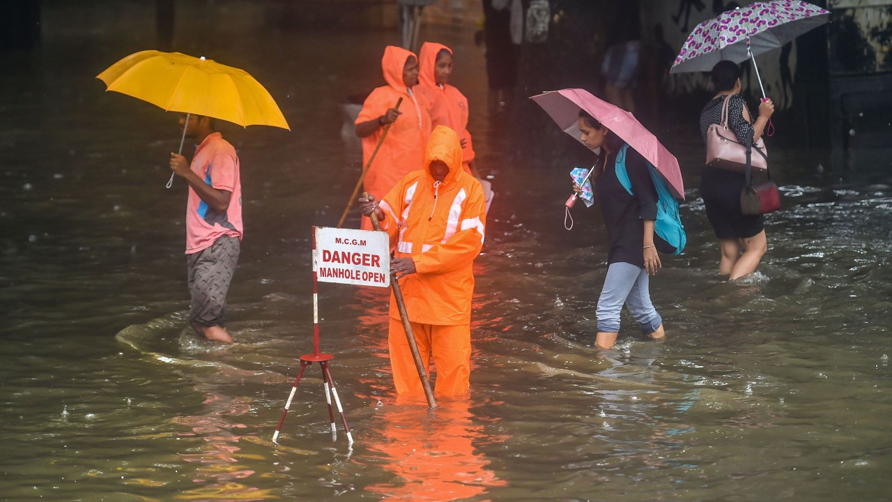A Municipal worker stands guard to warn pedestrians of an open manhole on a waterlogged street following heavy monsoon rains, in Mumbai on July 01, 2019. (Image: PTI)