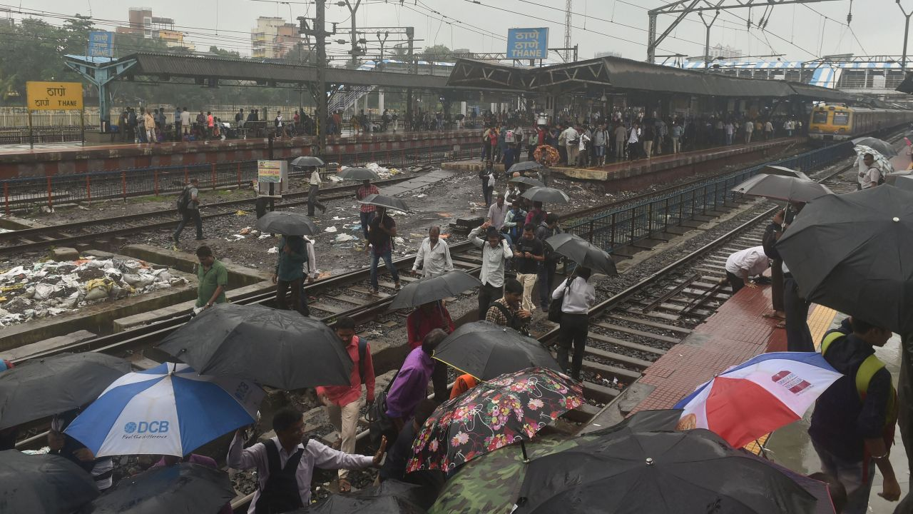 People walk on the railway tracks as heavy monsoon rains hit the central suburban trains service. (Image: PTI)
