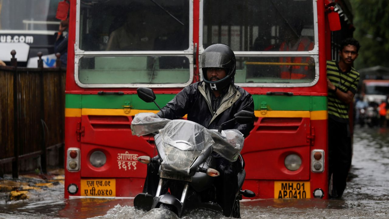 A man rides a motorcycle through a water-logged street during heavy rains. (Image: Reuters)