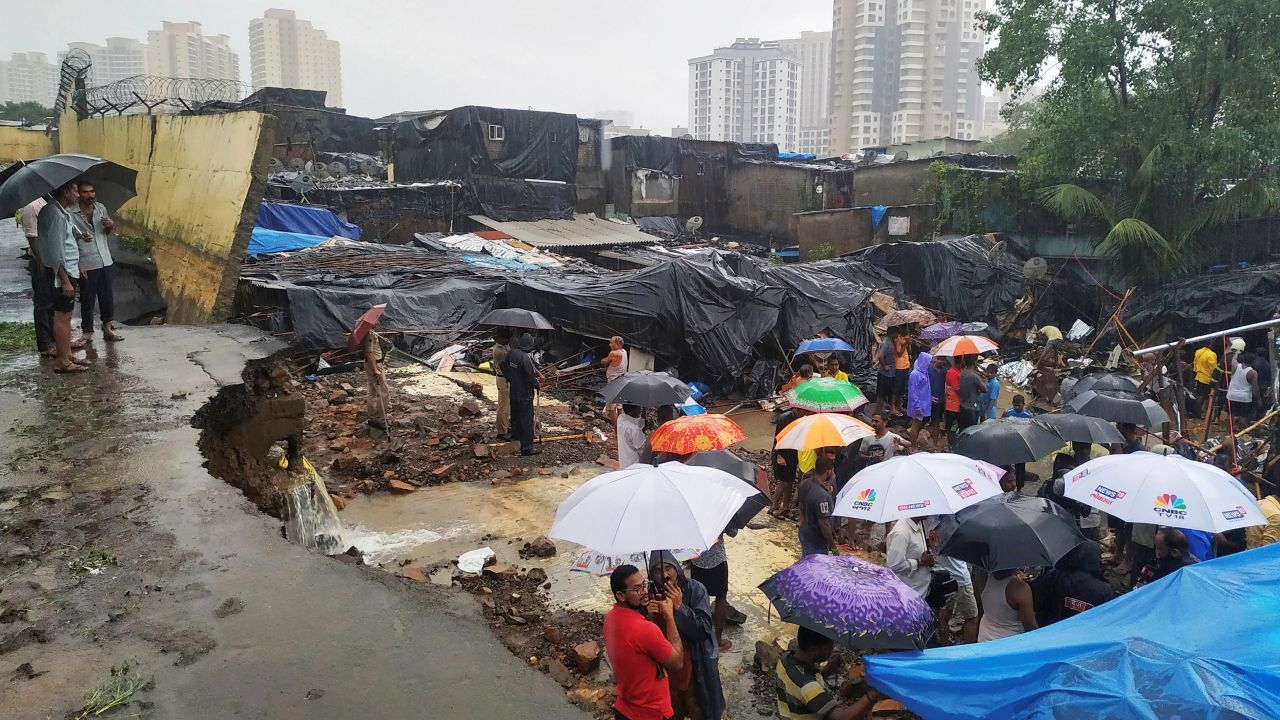 People stand among the debris after a wall collapsed on hutments due to heavy rains in Mumbai. (Image: Reuters)