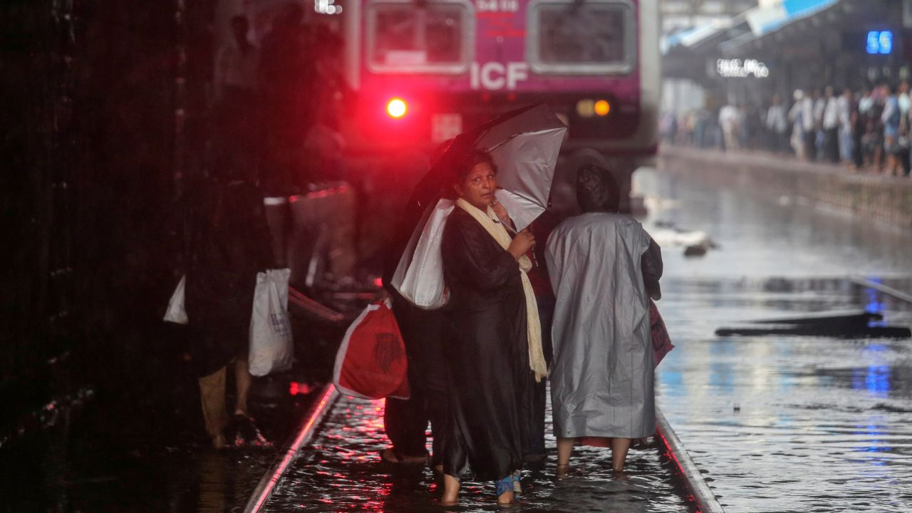 Commuters cross waterlogged railway tracks as a suburban train is seen parked at a railway station after its services were suspended during heavy monsoon rains. (Image: Reuters)