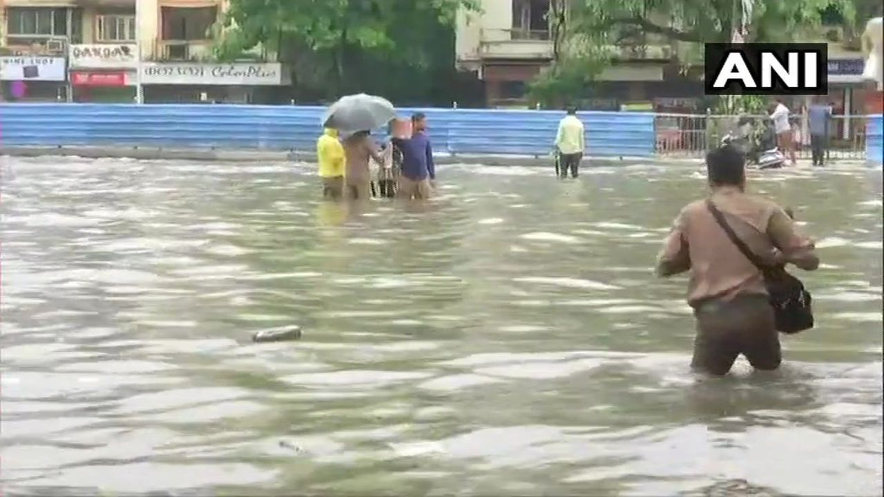 Streets in the city flooded due to heavy rainfall, people wade through water in Gandhi Market area, Sion. (Image: ANI)